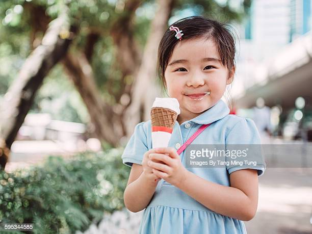 Lovely little girl having ice-cream joyfully