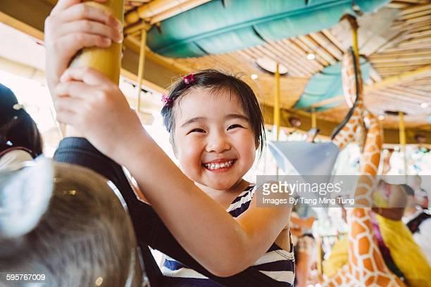 Lovely little girl riding on a carousel joyfully