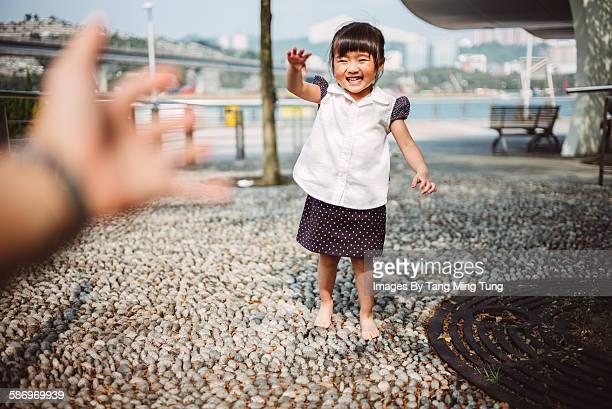 Lovely little girl walking towards parent