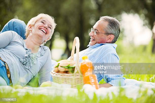 Lovely mature couple having a picnic in park.