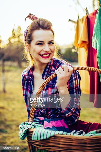 Lovely retro style girl with a laundry basket outdoors : Stock Photo