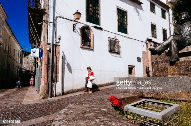 MONDOñEDO LUGO GALICIA SPAIN Lovely senior couple walking by Alvaro Cunqueiro sculpture in Cathedral square