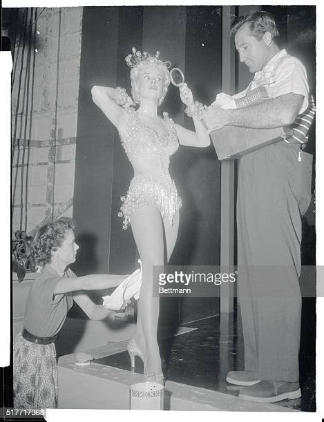 Lovely singing and dancing star Gloria DeHaven is carefully dabbed by makeup attendants as she prepares to go before the cameras on Paramount's set...