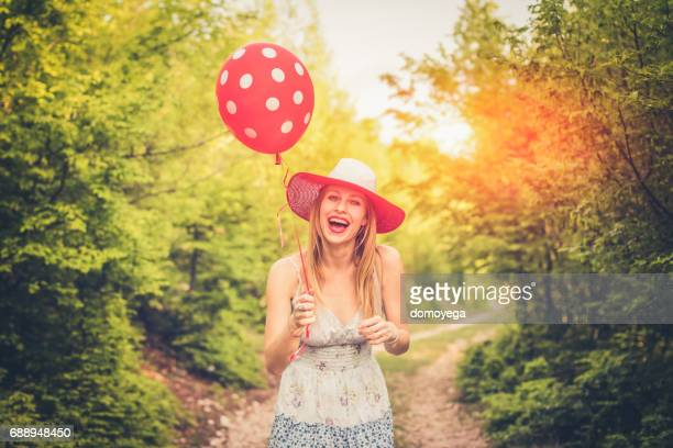 Lovely smiling woman with a hat holding balloon on a sunny day in country