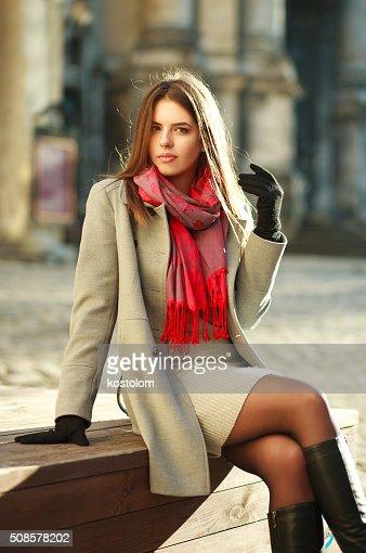 Lovely woman in coat sitting on city street in sunlight : Stock Photo