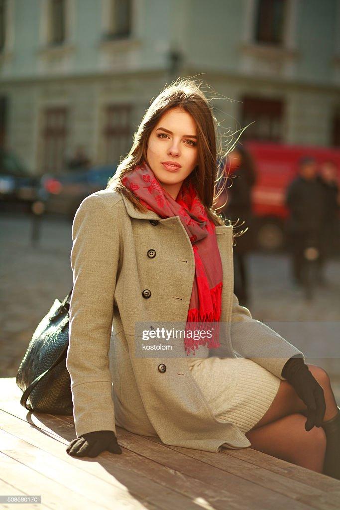 Lovely woman in coat sitting on city street in sunlight : Stockfoto