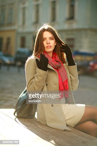 Lovely woman in coat sitting on city street in sunlight : Bildbanksbilder