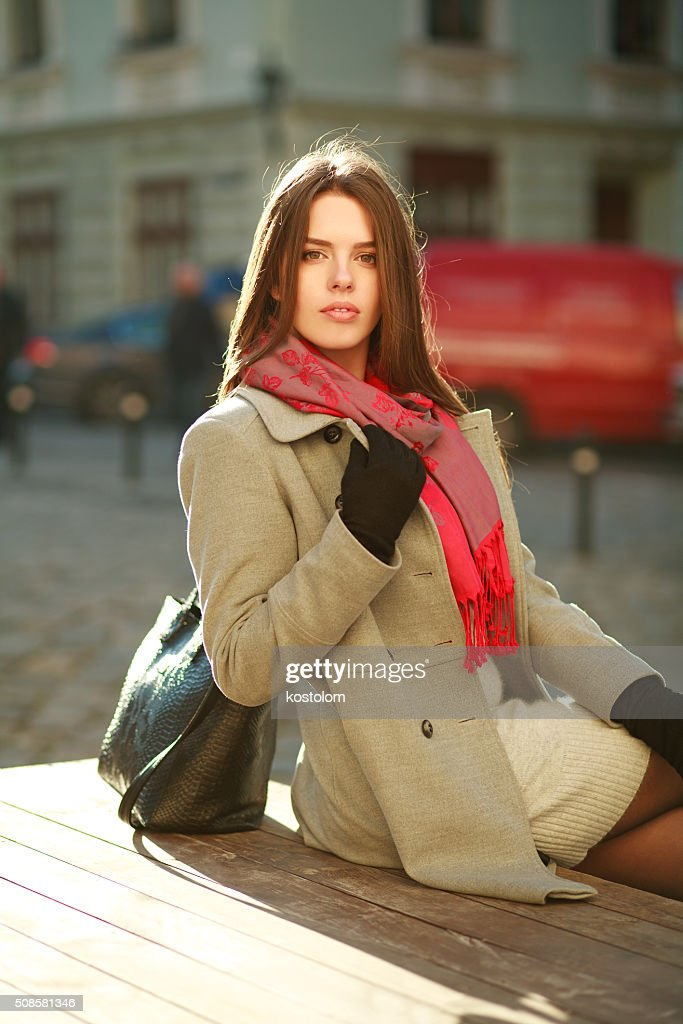 Lovely woman in coat sitting on city street in sunlight : Stock Photo