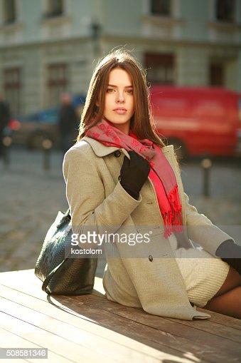 Bella donna in cappotto seduto sulla strada di città in luce solare : Foto stock