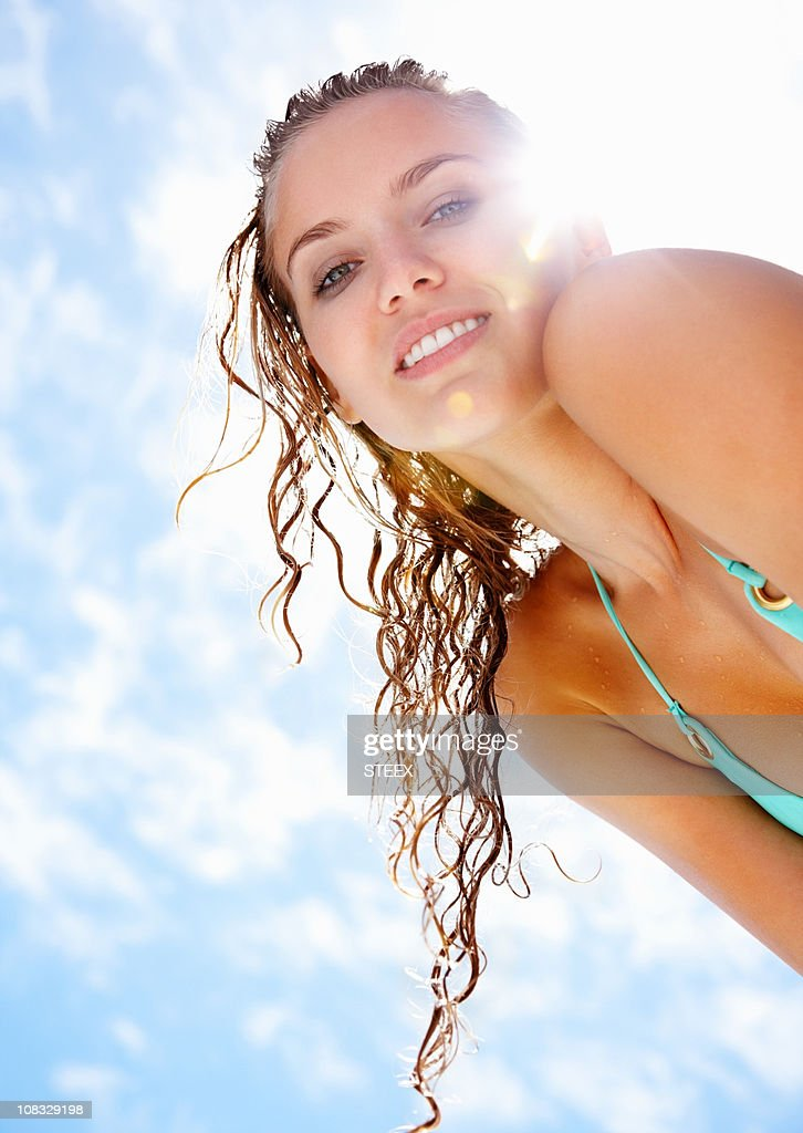 Lovely young female in bikini against cloudy sky : Stock Photo