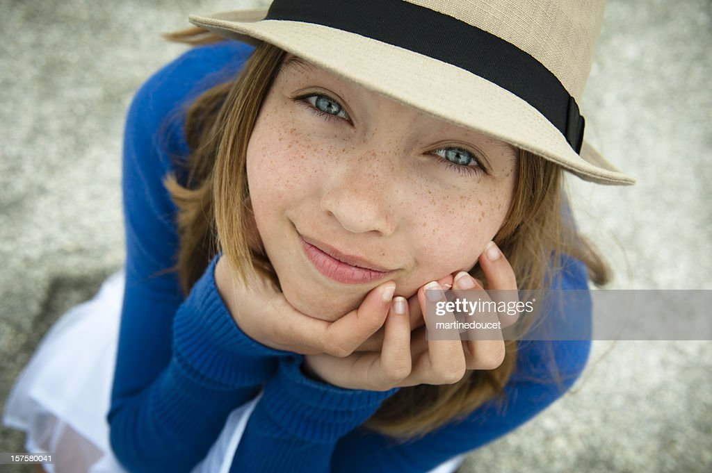 Lovely young girl with a hat looking up on beach. : Stock Photo
