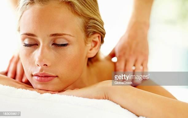 Jeune femme charmante relaxante lors d'un massage du corps