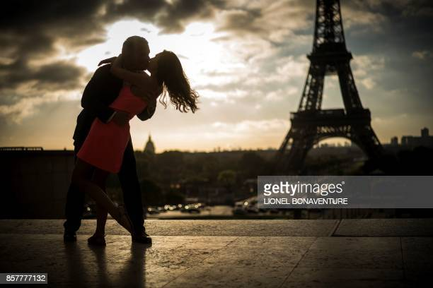 Lovers are pictured at sunrise at the eiffel tower on October 5 2017 in Paris / AFP PHOTO / Lionel BONAVENTURE