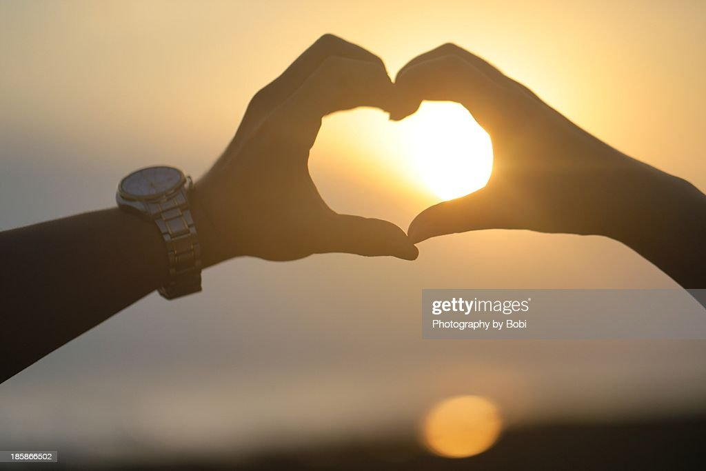 Lovers hand make a heart front the Sunset beach