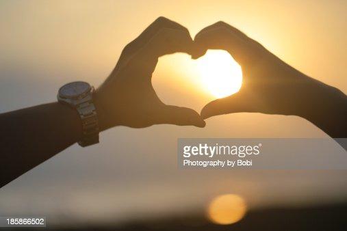 Lovers hand make a heart front the Sunset beach