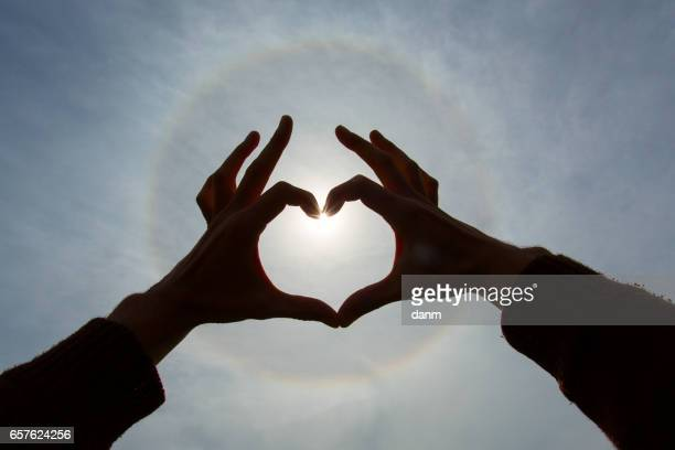 Lovers holding hands in shape of heart over a sunbow