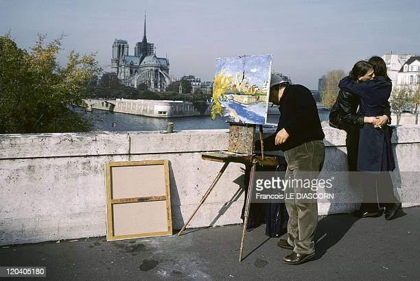Lovers in Paris France Lovers along the Seine Paris on the Tournelle Bridge A painter is painting the scene with Notre Dame in the background