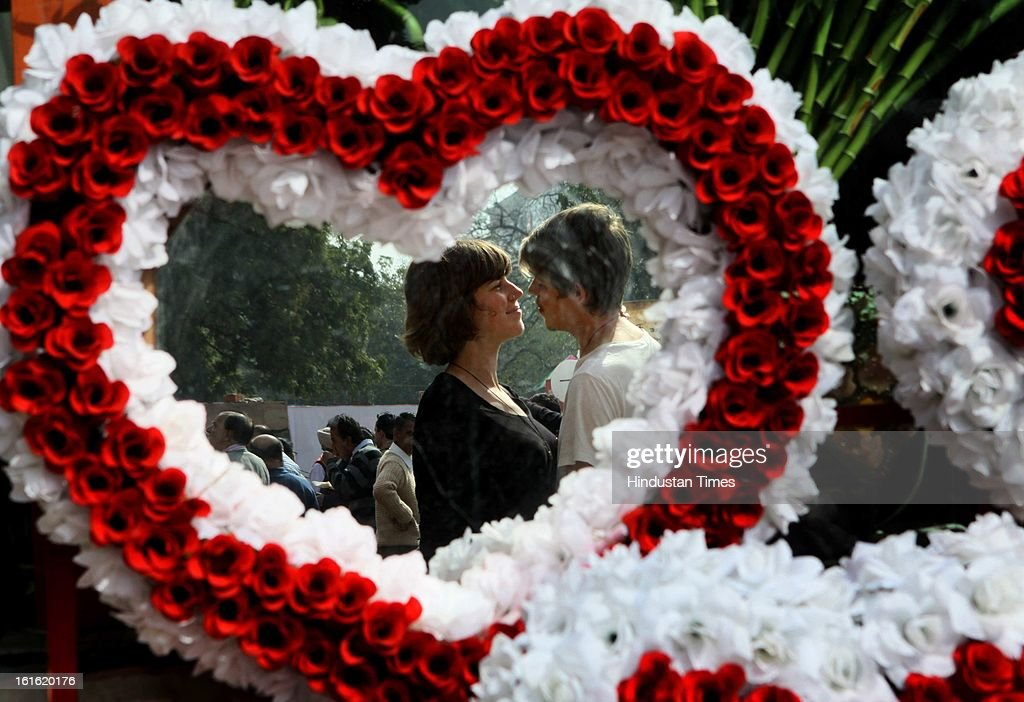 Lovers kissing as seen from the heart shaped bouquet as the city are all decked up for the Valentine's Day at Connaught Place on February 13, 2013 in New Delhi, India. In past decade the Valentine has gained popularity amongst younger as well older generation.
