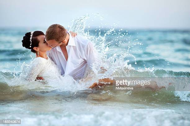 Lovers kissing in the waves