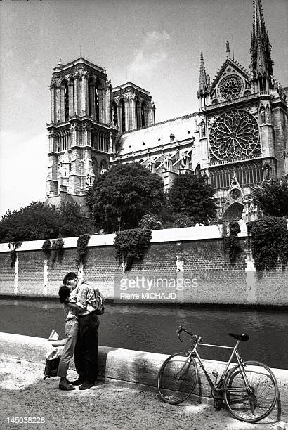 Lovers on the banks of the Seine river in front of Notre Dame Cathedral in Paris France