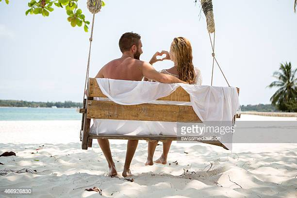 愛好家のベンチに座る作るハート型に手-トロピカルビーチ