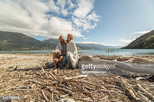 Lovers sitting on tree trunk by the lake