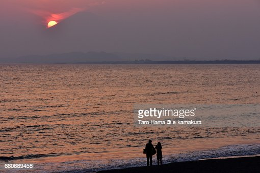 Lovers watching the evening sun sinking behind Mt. Fuji on the beach : ストックフォト