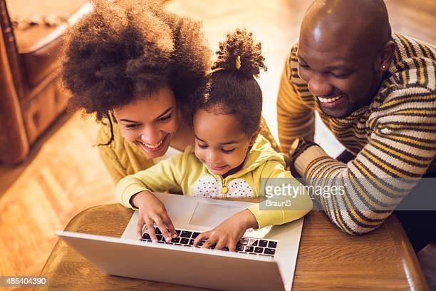 Liebevoll afrikanische amerikanische Eltern und ihre Tochter mit laptop.