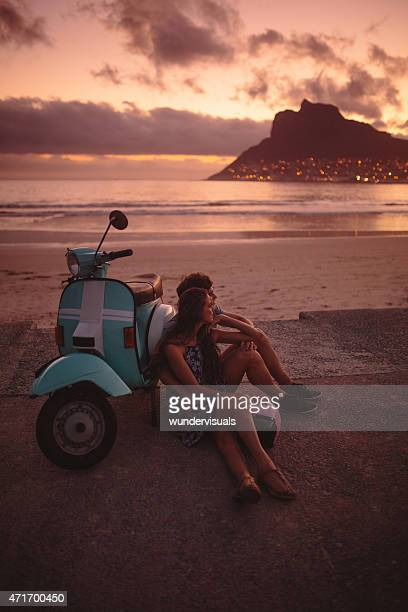 Loving couple at the beach with their scooter at sunset