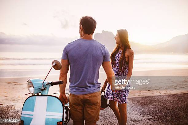 Loving couple at the beach with their scooter