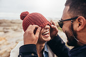 Loving couple having fun outdoors. Man covering eyes of woman with cap.
