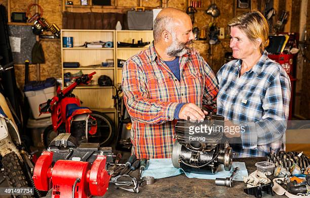 Loving couple in their motorcycle garage workshop.