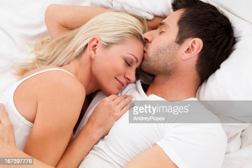 Loving couple lying in bed : Bildbanksbilder
