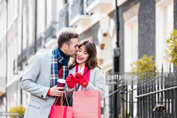 Liebespaar auf Stadtstraße mit Einkaufstüten und smart phone
