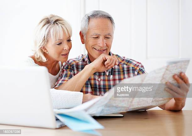 Loving couple planning vacation with map and laptop