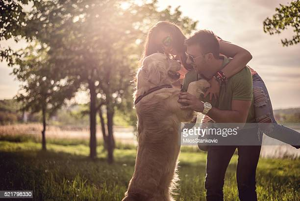 Loving couple playing with dog in field by the lake