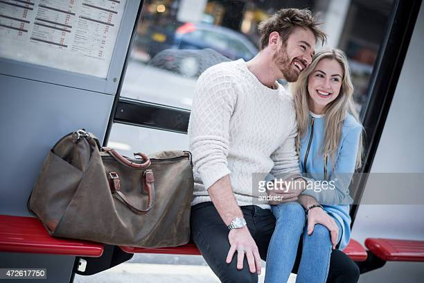 Loving couple sitting at the bus stop