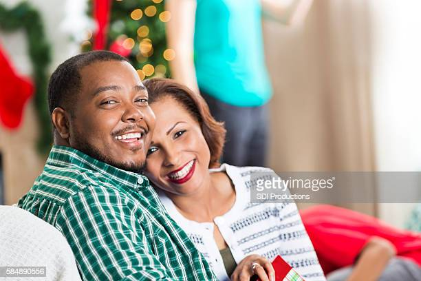 Loving couple snuggle on the couch at Christmastime