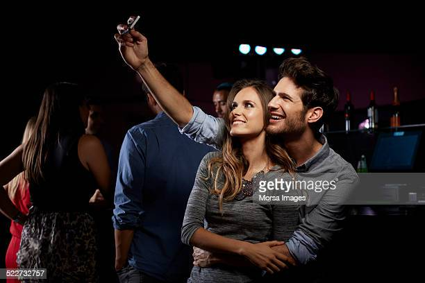 Loving couple taking self portrait in nightclub