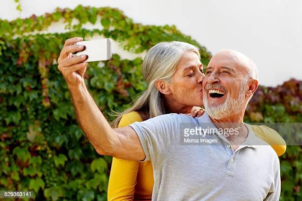 Loving couple taking selfie at yard