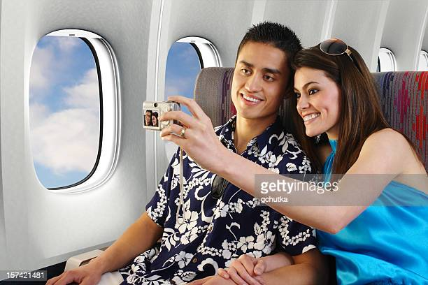 Loving couple taking selfie on plane in vacation