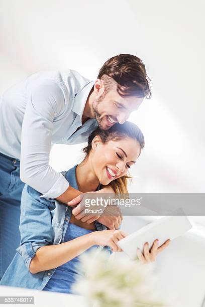 Loving couple using digital tablet.