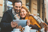 Joyful man and woman are watching tablet and laughing. They are sitting in cafe outdoors and hugging
