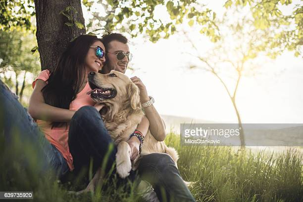 Loving couple with dog in field by the lake