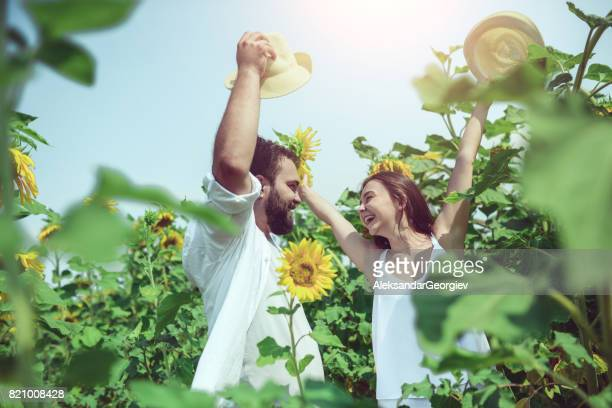Loving Couple with Raised Hats Having Fun in Sunflower Field