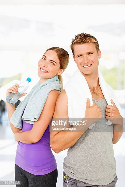 Loving Couple With Towels And Water Bottle In Gym