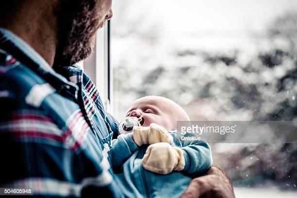 Amour père avec nouveau-né bébé près de la fenêtre en hiver