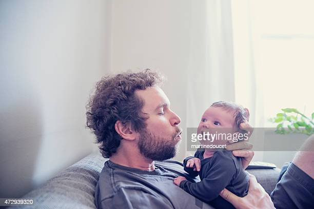 Loving dad with newborn baby on couch in livingroom.