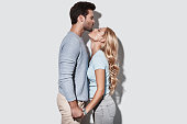 Beautiful young couple holding hands and kissing while standing against grey background
