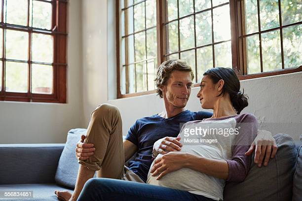 Loving expectant couple relaxing on sofa